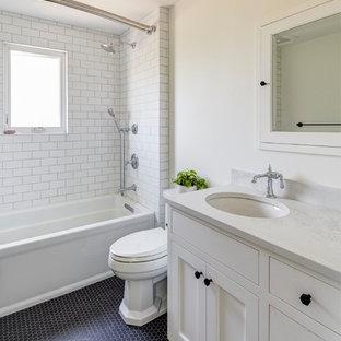 Inspiration för mellanstora klassiska vitt badrum med dusch, med luckor med infälld panel, vita skåp, ett badkar i en alkov, en dusch/badkar-kombination, en toalettstol med separat cisternkåpa, tunnelbanekakel, beige väggar, klinkergolv i porslin, ett undermonterad handfat, bänkskiva i kvartsit och svart golv