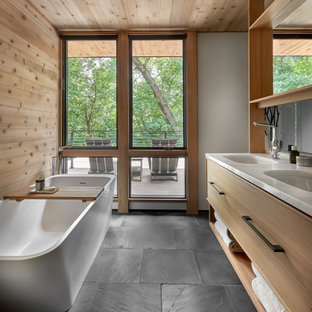 Example of a mid-sized mountain style master blue tile and terra-cotta tile slate floor, black floor, double-sink, wood ceiling and wood wall bathroom design in Chicago with flat-panel cabinets, light wood cabinets, a one-piece toilet, white walls, an undermount sink, marble countertops, a hinged shower door, white countertops and a floating vanity