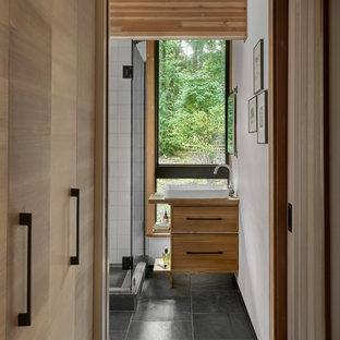 Идея дизайна: ванная комната среднего размера в стиле рустика с плоскими фасадами, светлыми деревянными фасадами, угловым душем, унитазом-моноблоком, белой плиткой, керамогранитной плиткой, белыми стенами, полом из сланца, душевой кабиной, настольной раковиной, столешницей из дерева, черным полом, душем с распашными дверями, коричневой столешницей, нишей, тумбой под одну раковину, напольной тумбой, балками на потолке и деревянными стенами