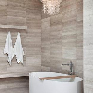 Foto de cuarto de baño principal, actual, grande, con bañera exenta, ducha a ras de suelo, sanitario de una pieza, baldosas y/o azulejos grises, baldosas y/o azulejos de piedra, paredes grises y suelo de piedra caliza