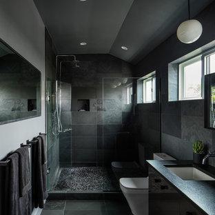 Ispirazione per una stanza da bagno padronale minimalista di medie dimensioni con ante lisce, ante nere, doccia doppia, WC monopezzo, piastrelle nere, piastrelle in ardesia, pareti grigie, pavimento in gres porcellanato, lavabo sottopiano, top in superficie solida, pavimento nero e porta doccia a battente
