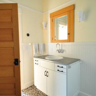 Modelo de cuarto de baño principal, ecléctico, de tamaño medio, con armarios con paneles lisos, puertas de armario blancas, ducha abierta, baldosas y/o azulejos de vidrio, paredes amarillas, lavabo encastrado, encimera de zinc, suelo gris y ducha abierta