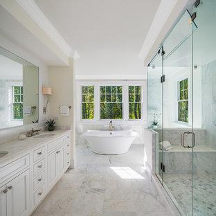 Idee per una grande stanza da bagno padronale chic con ante a filo, ante bianche, vasca freestanding, piastrelle bianche, piastrelle di marmo, pavimento in marmo, lavabo sottopiano, top in marmo, pavimento bianco, porta doccia a battente e pareti beige
