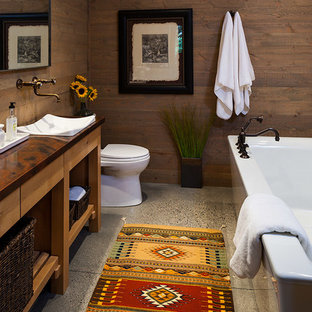 Example of a mid-sized mountain style concrete floor freestanding bathtub design in Other with open cabinets, brown walls, a vessel sink, copper countertops and light wood cabinets