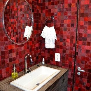 Diseño de cuarto de baño con ducha, bohemio, de tamaño medio, con armarios con paneles lisos, puertas de armario con efecto envejecido, sanitario de una pieza, baldosas y/o azulejos rojos, baldosas y/o azulejos en mosaico, paredes rojas, lavabo encastrado y encimera de madera