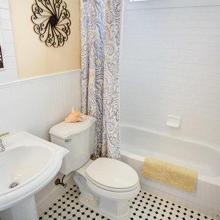Foto de cuarto de baño con ducha, tradicional renovado, pequeño, con baldosas y/o azulejos blancos, bañera empotrada, combinación de ducha y bañera, sanitario de una pieza, baldosas y/o azulejos de cemento, paredes amarillas, suelo con mosaicos de baldosas, lavabo con pedestal, suelo blanco y ducha con cortina