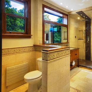 Idee per una grande stanza da bagno padronale moderna con lavabo sottopiano, consolle stile comò, ante in legno scuro, top in marmo, vasca sottopiano, WC a due pezzi, piastrelle marroni, piastrelle in pietra, pareti marroni e pavimento in pietra calcarea