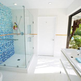 Inredning av ett modernt mellanstort badrum för barn, med en vägghängd toalettstol, vit kakel, blå kakel, orange kakel, vita väggar, släta luckor, vita skåp, en hörndusch, porslinskakel, klinkergolv i porslin, ett integrerad handfat och bänkskiva i akrylsten