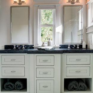 Diseño de cuarto de baño principal, clásico renovado, de tamaño medio, con armarios con rebordes decorativos, puertas de armario blancas, paredes blancas, suelo de baldosas de cerámica, lavabo bajoencimera, encimera de esteatita y suelo blanco