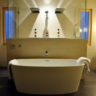 Immagine di una grande stanza da bagno padronale minimalista con vasca freestanding, doccia doppia, piastrelle beige, piastrelle in ceramica, pareti beige e pavimento con piastrelle in ceramica