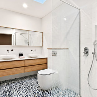 Photo of a country bathroom in Perth with flat-panel cabinets, medium wood cabinets, a curbless shower, a one-piece toilet, white tile, white walls, cement tiles, a vessel sink, multi-coloured floor, an open shower and white benchtops.