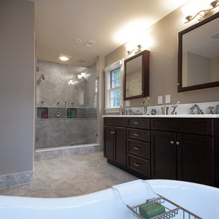 Example of a large classic master gray tile and porcelain tile porcelain tile bathroom design in DC Metro with recessed-panel cabinets, dark wood cabinets, a two-piece toilet, gray walls, an undermount sink and solid surface countertops