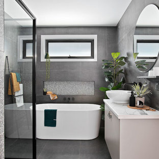 Photo of a small contemporary master bathroom in Other with a freestanding tub, a corner shower, gray tile, ceramic tile, ceramic floors, grey floor, a hinged shower door, flat-panel cabinets, grey cabinets, a vessel sink, laminate benchtops and white benchtops.