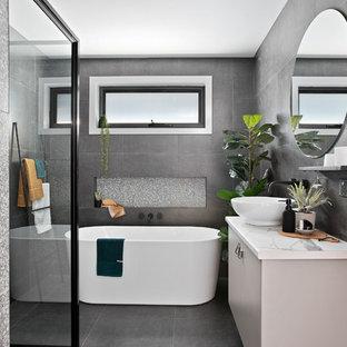 Неиссякаемый источник вдохновения для домашнего уюта: маленькая главная ванная комната в современном стиле с отдельно стоящей ванной, угловым душем, серой плиткой, керамической плиткой, полом из керамической плитки, серым полом, душем с распашными дверями, плоскими фасадами, серыми фасадами, настольной раковиной, столешницей из ламината и белой столешницей