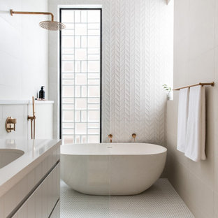 Mid-sized contemporary master wet room bathroom in Sydney with flat-panel cabinets, grey cabinets, a freestanding tub, white tile, porcelain tile, porcelain floors, an undermount sink, white floor, an open shower, beige benchtops, a single vanity and a floating vanity.