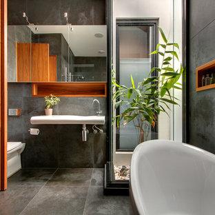 Idéer för funkis badrum, med ett väggmonterat handfat, skåp i mellenmörkt trä, ett fristående badkar, grå kakel, grå väggar och en toalettstol med hel cisternkåpa