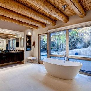 Foto di un'ampia stanza da bagno padronale stile americano con ante lisce, ante in legno bruno, vasca freestanding, pareti bianche, pavimento in gres porcellanato e lavabo sottopiano
