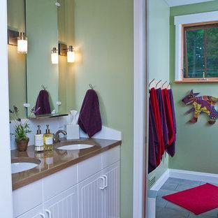 Modelo de cuarto de baño infantil, de estilo americano, de tamaño medio, con armarios con paneles lisos, puertas de armario blancas, baldosas y/o azulejos grises, paredes verdes, lavabo bajoencimera y suelo de madera en tonos medios
