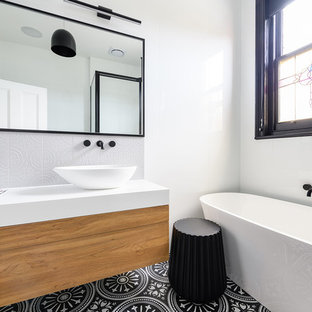 Inspiration for a contemporary bathroom in Hobart with flat-panel cabinets, medium wood cabinets, a freestanding tub, white tile, white walls, a vessel sink, multi-coloured floor and white benchtops.