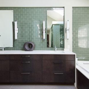 Foto di una stanza da bagno padronale minimal di medie dimensioni con lavabo sottopiano, ante lisce, ante in legno bruno, top in quarzo composito, vasca da incasso, piastrelle verdi, piastrelle di vetro, pareti verdi e pavimento in gres porcellanato