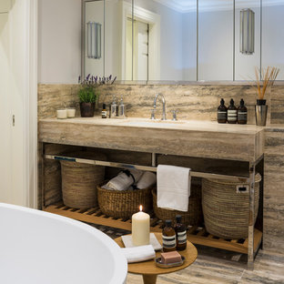Photo of a contemporary bathroom in London with a freestanding bath, grey walls and a submerged sink.