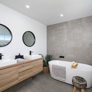 Photo of a beach style bathroom in Sydney with flat-panel cabinets, medium wood cabinets, a freestanding tub, gray tile, white walls, a vessel sink, wood benchtops, grey floor and brown benchtops.