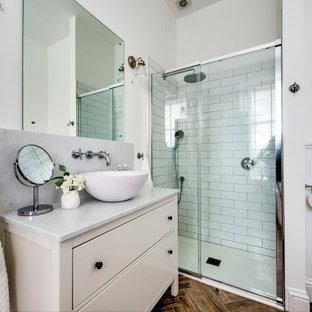 Immagine di una stanza da bagno con doccia chic con consolle stile comò, ante beige, doccia alcova, WC sospeso, piastrelle bianche, piastrelle diamantate, pareti bianche, lavabo a bacinella, pavimento marrone, porta doccia scorrevole e top grigio