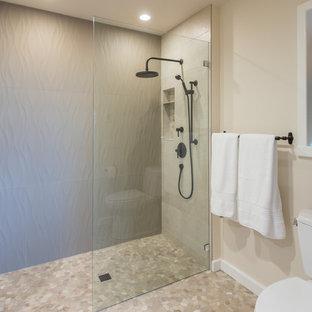 シアトルの大きいモダンスタイルのおしゃれなマスターバスルーム (シェーカースタイル扉のキャビネット、中間色木目調キャビネット、アルコーブ型浴槽、バリアフリー、分離型トイレ、ベージュのタイル、磁器タイル、ベージュの壁、玉石タイル、アンダーカウンター洗面器、珪岩の洗面台、マルチカラーの床、オープンシャワー) の写真