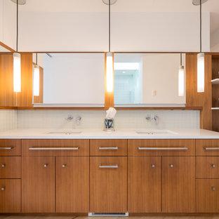 Ejemplo de cuarto de baño actual con armarios con paneles lisos, puertas de armario de madera oscura, paredes blancas, suelo de madera clara, lavabo bajoencimera, suelo beige y encimeras blancas