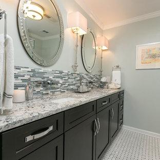 Idee per una stanza da bagno chic di medie dimensioni con lavabo da incasso, ante con riquadro incassato, ante nere, top in granito, vasca da incasso, vasca/doccia, piastrelle grigie, piastrelle a listelli, pareti grigie e pavimento con piastrelle in ceramica