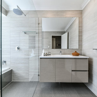This is an example of a contemporary bathroom in Perth with flat-panel cabinets, an alcove tub, an open shower, beige tile, gray tile and an undermount sink.