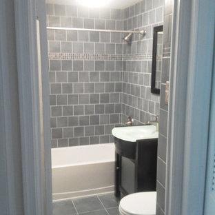 Inredning av ett klassiskt mellanstort badrum med dusch, med släta luckor, svarta skåp, ett badkar i en alkov, en dusch/badkar-kombination, en toalettstol med separat cisternkåpa, grå kakel, porslinskakel, grå väggar, klinkergolv i porslin, ett integrerad handfat, bänkskiva i glas, grått golv och dusch med duschdraperi