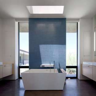 Example of a minimalist blue tile and mosaic tile concrete floor freestanding bathtub design in Phoenix with a vessel sink, flat-panel cabinets, light wood cabinets and white walls