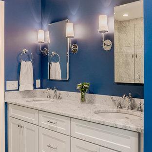 Modelo de cuarto de baño principal, tradicional renovado, de tamaño medio, con armarios con paneles lisos, puertas de armario blancas, sanitario de una pieza, baldosas y/o azulejos grises, baldosas y/o azulejos de cerámica, paredes azules, suelo de baldosas de cerámica, lavabo bajoencimera y encimera de granito