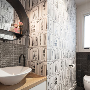 This is an example of a contemporary bathroom in Melbourne with flat-panel cabinets, white cabinets, black tile, white walls, a vessel sink, wood benchtops, black floor and beige benchtops.