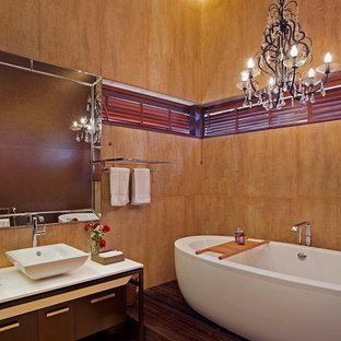 バンガロールのトロピカルスタイルのおしゃれなマスターバスルーム (家具調キャビネット、濃色木目調キャビネット、置き型浴槽、オレンジの壁、ベッセル式洗面器) の写真