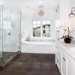 Klassisk inredning av ett grå grått badrum, med ett undermonterad handfat, skåp i shakerstil, vita skåp, ett badkar i en alkov, en dusch i en alkov och brunt golv