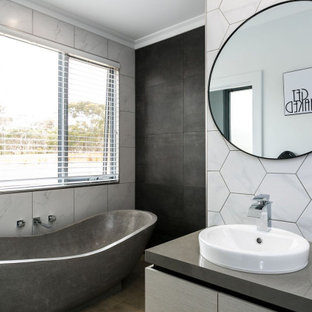 Design ideas for a mid-sized contemporary master bathroom in Adelaide with flat-panel cabinets, grey cabinets, a freestanding tub, an open shower, a one-piece toilet, gray tile, porcelain tile, grey walls, porcelain floors, a drop-in sink, solid surface benchtops, brown floor, an open shower, grey benchtops, a single vanity and a built-in vanity.