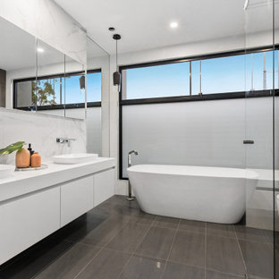 Photo of a large contemporary master bathroom in Melbourne with white cabinets, a freestanding tub, a corner shower, white tile, porcelain floors, marble benchtops, grey floor, a hinged shower door, white benchtops, flat-panel cabinets, a one-piece toilet and a vessel sink.
