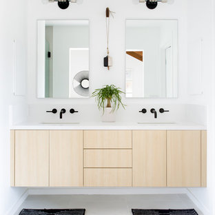 Medium sized scandi bathroom in Los Angeles with flat-panel cabinets, light wood cabinets, white tiles, white walls, ceramic flooring, a submerged sink, engineered stone worktops, white floors, a freestanding bath and a hinged door.