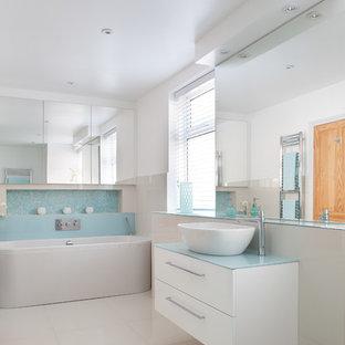 Inspiration för ett mellanstort funkis blå blått badrum, med ett fristående handfat, bänkskiva i glas, ett fristående badkar, en vägghängd toalettstol, vit kakel, blå kakel, klinkergolv i porslin, släta luckor, vita skåp och vita väggar