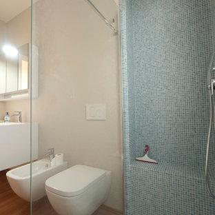 Foto de cuarto de baño principal, moderno, de tamaño medio, con lavabo integrado, armarios con paneles lisos, puertas de armario blancas, encimera de cuarzo compacto, ducha abierta, sanitario de pared, baldosas y/o azulejos azules, baldosas y/o azulejos de vidrio, paredes beige y suelo de bambú