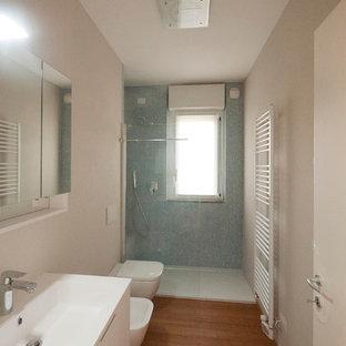 Modelo de cuarto de baño principal, minimalista, de tamaño medio, con lavabo integrado, armarios con paneles lisos, puertas de armario blancas, encimera de cuarzo compacto, ducha abierta, sanitario de pared, baldosas y/o azulejos azules, baldosas y/o azulejos de vidrio, paredes beige y suelo de bambú