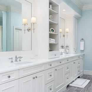 Diseño de cuarto de baño principal, costero, grande, con armarios tipo mueble, puertas de armario blancas, bañera encastrada sin remate, ducha abierta, sanitario de una pieza, baldosas y/o azulejos grises, baldosas y/o azulejos de porcelana, paredes azules, suelo de baldosas de porcelana, lavabo bajoencimera y encimera de vidrio