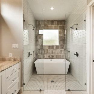 Immagine di una stanza da bagno padronale tradizionale con ante in stile shaker, vasca freestanding, doccia doppia, piastrelle beige, piastrelle di pietra calcarea, pareti beige, pavimento in gres porcellanato, lavabo sottopiano, top in pietra calcarea, pavimento beige e doccia aperta
