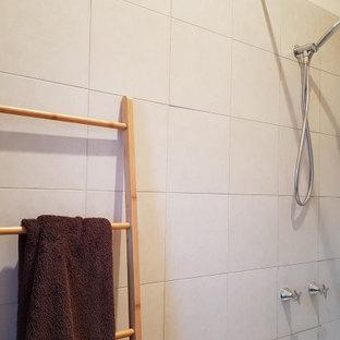 Esempio di una stanza da bagno con doccia minimal di medie dimensioni con lavabo sospeso, ante lisce, ante arancioni, top piastrellato, vasca da incasso, vasca/doccia, WC sospeso, piastrelle multicolore, piastrelle in ceramica, pavimento in gres porcellanato, pareti bianche, pavimento grigio, doccia con tenda e top grigio