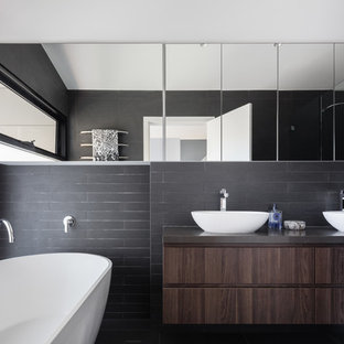 Design ideas for a contemporary master bathroom in Sydney with flat-panel cabinets, dark wood cabinets, a freestanding tub, an alcove shower, black tile, black walls and a vessel sink.