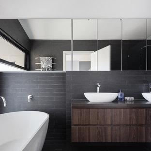 Idee per una stanza da bagno padronale contemporanea con ante lisce, ante in legno bruno, vasca freestanding, doccia alcova, piastrelle nere, pareti nere, lavabo a bacinella, porta doccia a battente e top nero