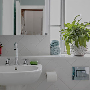 This is an example of a small classic family bathroom in Hampshire with a built-in bath, a shower/bath combination, a one-piece toilet, white tiles, ceramic tiles, green walls, vinyl flooring, a wall-mounted sink and green floors.