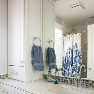 На фото: со средним бюджетом маленькие детские ванные комнаты в стиле современная классика с врезной раковиной, фасадами с утопленной филенкой, белыми фасадами, столешницей из переработанного стекла, ванной в нише, душем над ванной, унитазом-моноблоком, синей плиткой, стеклянной плиткой, серыми стенами и полом из известняка
